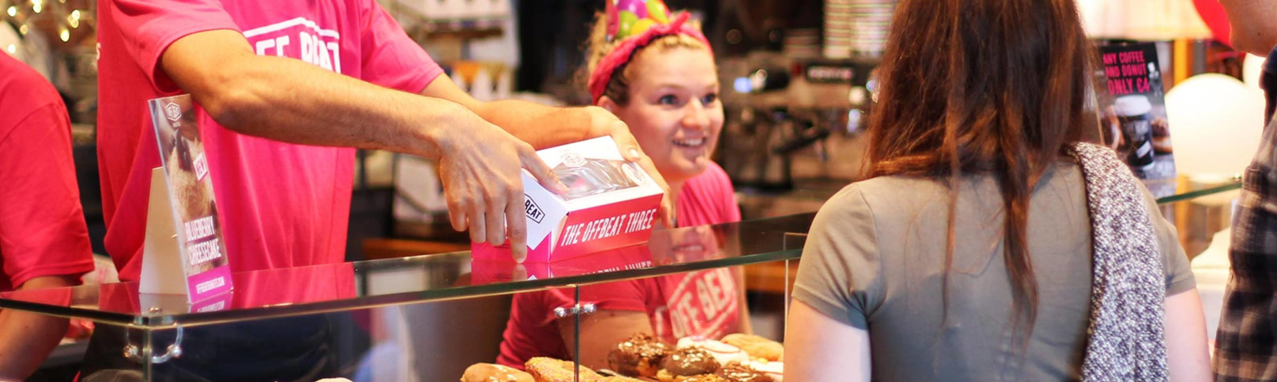 Offbeat Donut's employee serving a costumer